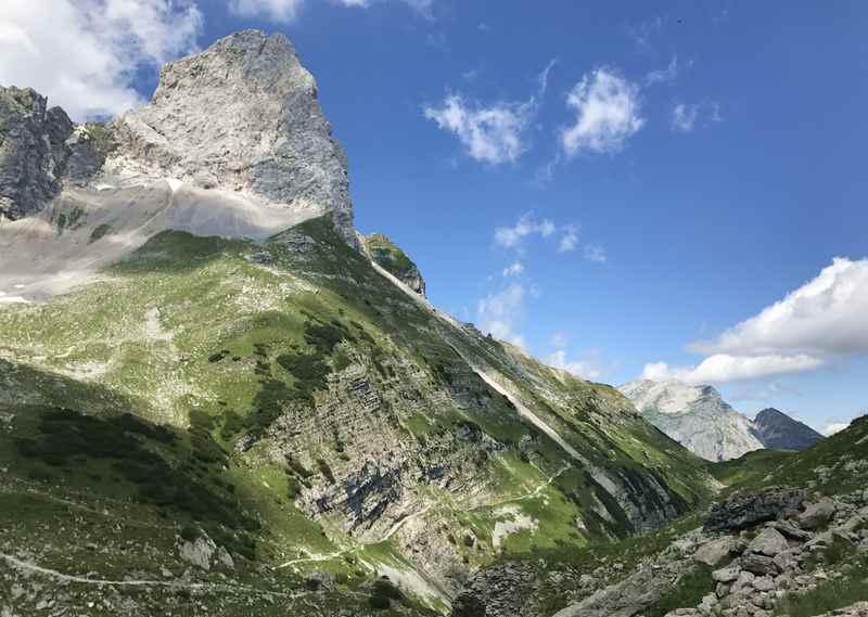 Gegenüber der Lamsenspitze wandern im Karwendel. Von hier sieht man klein den Wanderweg, der sich rund um die Lamsenspitze zwischen den beiden Lamsenjöchern zieht